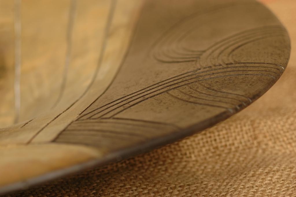 Particolare di un piatto in argilla semirefrattaria decorato con smalto oro raku